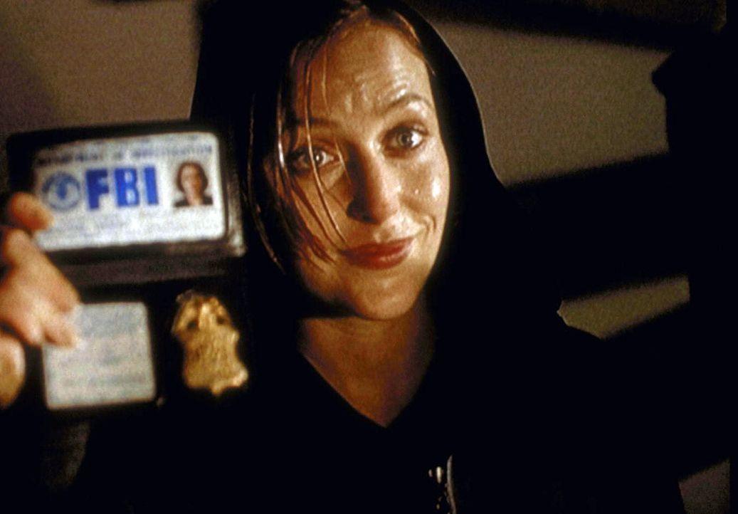 Da ein Polizist ihr nicht glauben will, weist sich Scully (Gillian Anderson) als FBI-Agentin aus. - Bildquelle: TM +   2000 Twentieth Century Fox Film Corporation. All Rights Reserved.