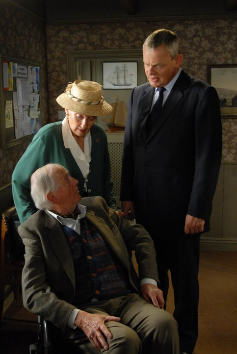 Kann Doc Martin (Martin Clunes, r.) Mrs. McLynn (Phyllida Law, l.) und ihrem Gatten (Benjamin Whitrow, sitzend) bei der Beschaffung eines Behinderte... - Bildquelle: BUFFALO PICTURES/ITV