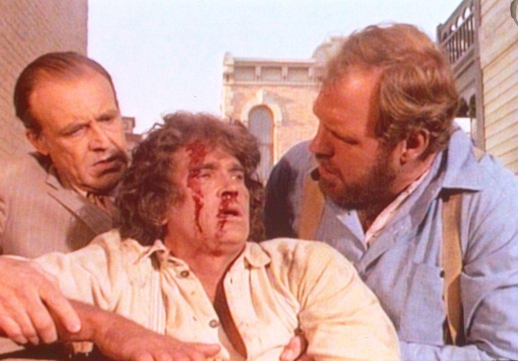 Charles (Michael Landon, M.) wurde niedergeschlagen. Jonathan (Merlin Olsen, r.) und Mr. Oleson (Richard Bull, l.) helfen ihm wieder auf die Beine. - Bildquelle: Worldvision