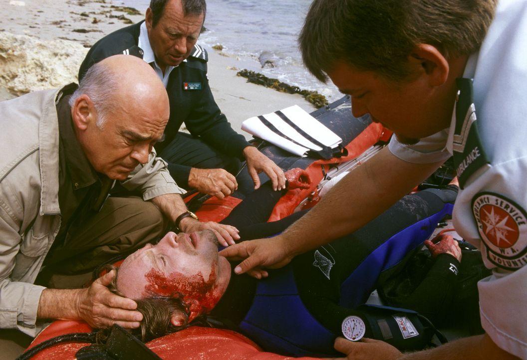 Entsetzt muss George (Peer Jäger, l.) seinen beim Tauchen schwer verunglückten Sohn Kyle (Julian Weigend, 2.v.r.) in die Obhut der Sanitäter übergeb... - Bildquelle: Megan Lewis Sat.1