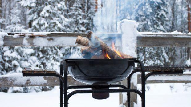 Ein mit brennenden Holzscheiten gefüllter Metallgrill steht vor einer verschn...