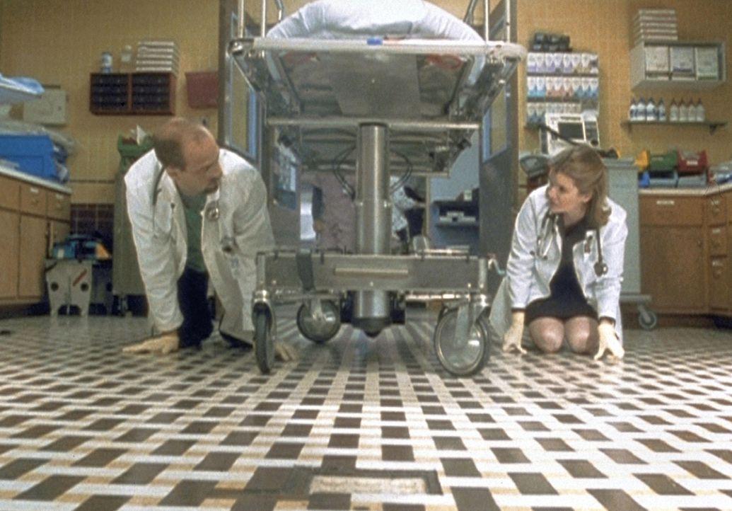 Dr. Greene (Anthony Edwards, l.) gibt sich alle Mühe, aber auch er kann den verlorenen Ohrring der neuen Chefärztin Dr. Lee (Mare Winningham, r.) ni... - Bildquelle: TM+  2000 WARNER BROS.