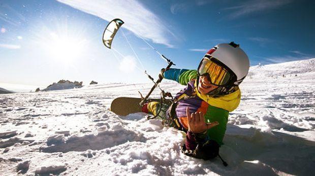 Mann liegt in Skianzug mit Snowbaord im Schnee, ein Kite-Drachen steigt in di...