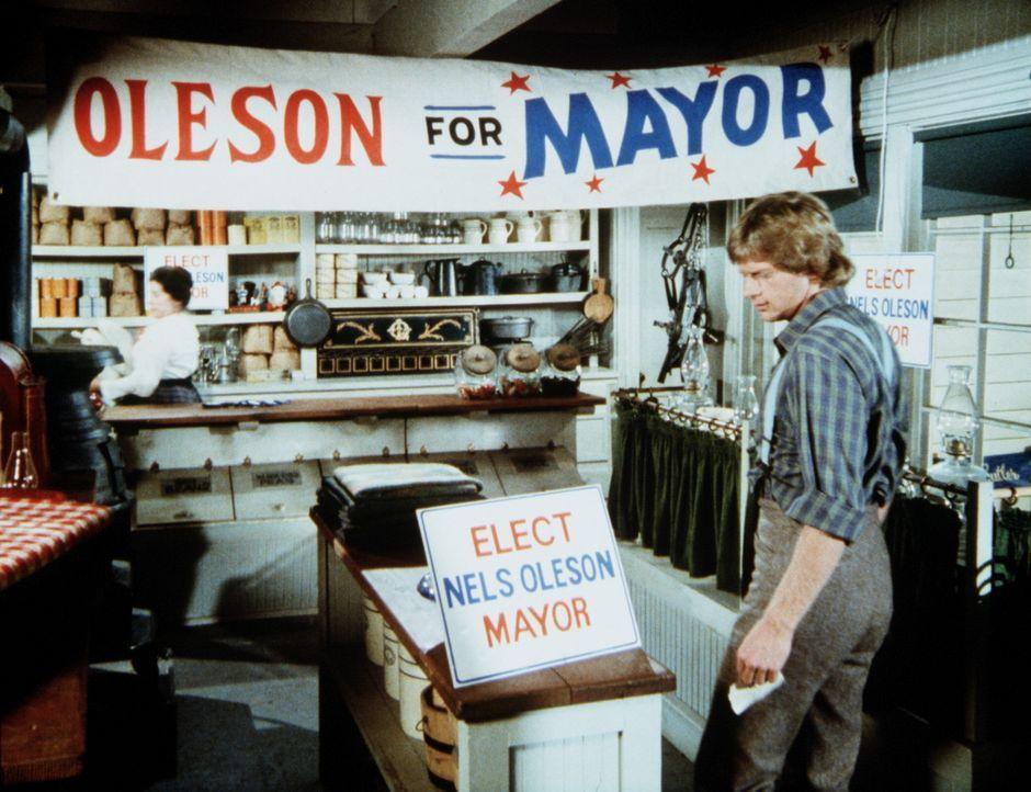 Almanzo (Dean Butler, r.) kommt zu Mrs. Oleson (Katherine MacGregor, l.) in den Laden und erfährt, dass er ebenfalls für das Bürgermeisteramt kan... - Bildquelle: Worldvision