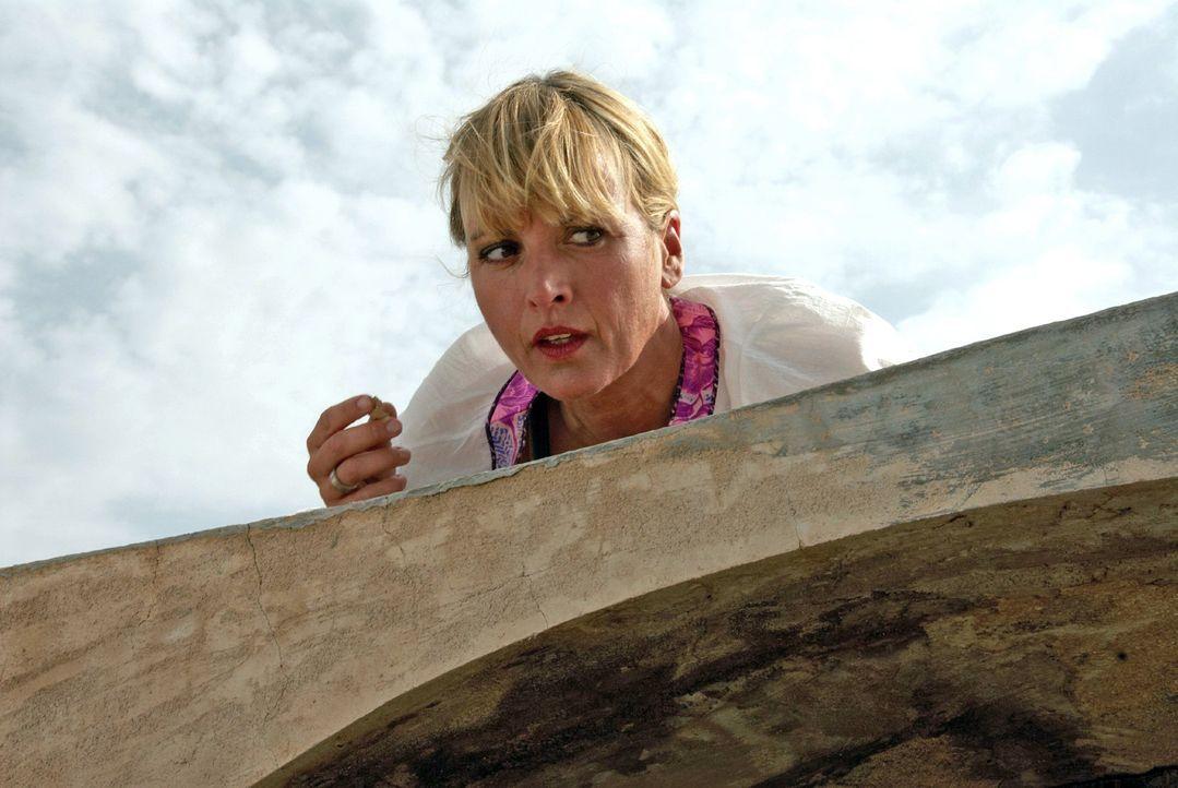 Nadine (Katharina Abt) kriecht über das Dach und versucht durch das Fenster in das Innere der Hütte zu sehen ...