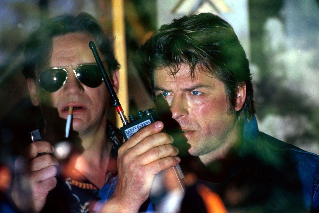 Die Kommissare Behrends (Hannes Hellmann, l.) und Jupp (Uwe Fellensiek, r.) beobachten mit einem Teleobjektiv die vermeintliche Drogenübergabe. - Bildquelle: Dobrivoie Kerpenisan Sat.1