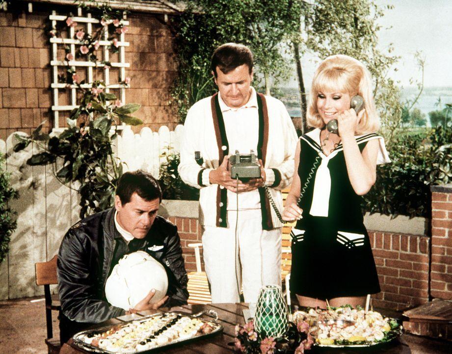 Jeannie (Barbara Eden, r.) und Roger (Bill Daily, M.) sind mit den Vorbereitungen einer Party beschäftigt und Tony (Larry Hagman, l.) wird prompt da... - Bildquelle: Columbia Pictures