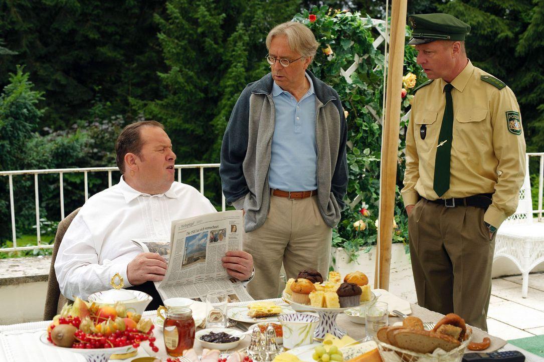 Benno (Ottfried Fischer, l.) sitzt mit Rambold (Gerd Anthoff, M.) beim Frühstück, als Schmidt (Norbert Mahler, r.) ihm die alte Zeitung vorbeibringt, die seine Theorie bestätigt ...