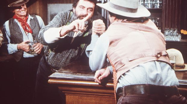 Mr. Edwards (Victor French, M.) misst sich im Saloon beim Armdrücken. © World...