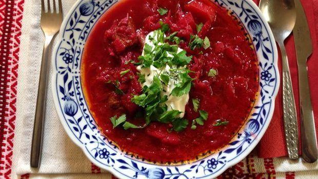 Rote Borschtsch Suppe mit typischer Garnitur: Schmand und Petersilie