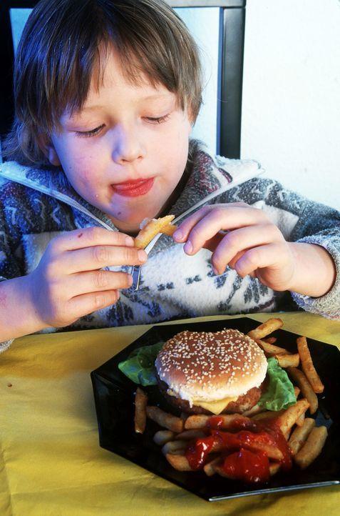 Junge isst einen Burger mit Pommes - Bildquelle: dpa-gms