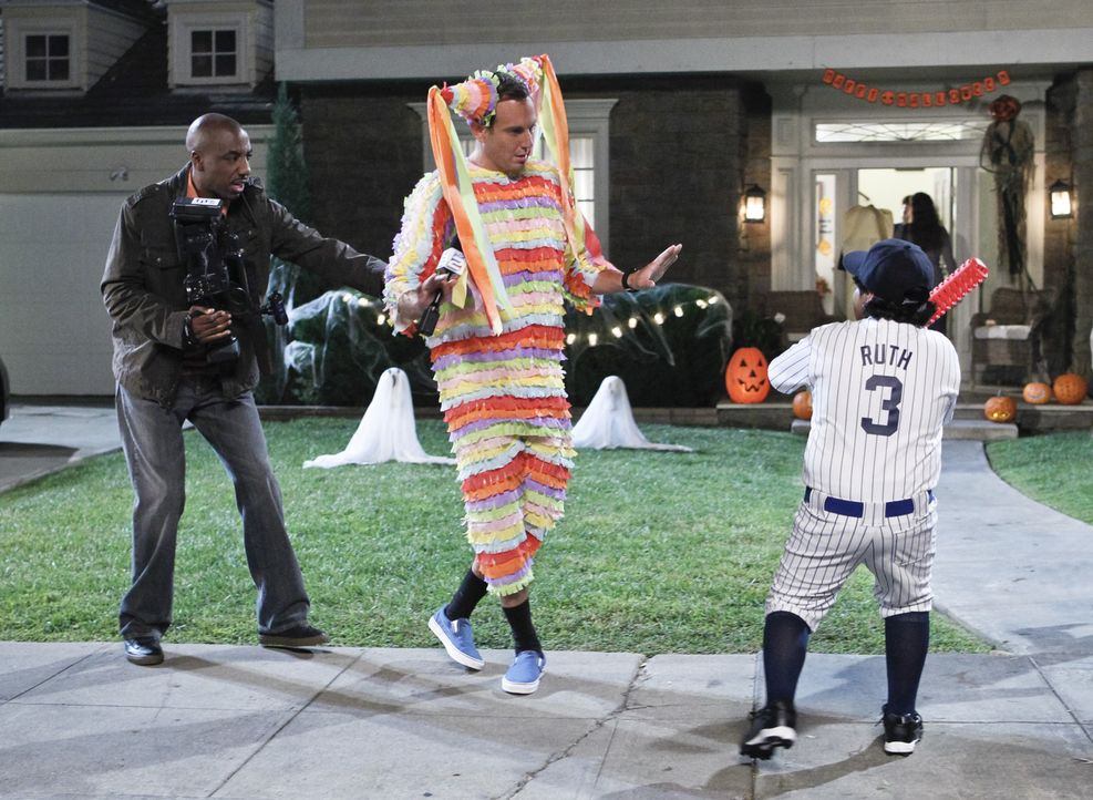 Als lebendige Pinata verkleidet, berichtet Nathan (Will Arnett, M.) mit seinem Kollegen Ray (J.B. Smoove, l.) live an Halloween. Was die Nacht dann... - Bildquelle: 2013 CBS Broadcasting, Inc. All Rights Reserved.